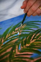 Close up of artist painting shrub with paintbrush and oil paints