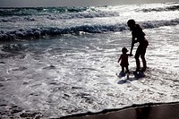 Mother and child playing in ocean