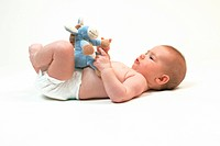 Baby lying on back, playing with soft toy