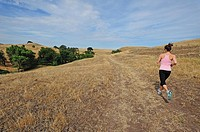 Woamn jogging on ranch cattle trail, Oakdale, California, USA