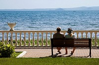 Couple, back to camera, sat on bench overlooking Lake Bolsena, Lazio, Italy