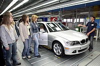A member of staff at the BMW AG during the Girl's Day on April 27, 2006, showing girl students a 3 series BMW car on the production line in Regensburg...