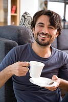 Man cosily drinking a cup of coffee