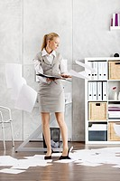 Young woman in office letting documents fall, front view