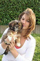 Lhasa Apso Canis lupus f. familiaris, young woman holding puppy on arm