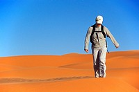 female tourist walking through sand dunes, Libya