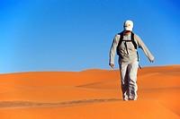 female tourist walking through sand dunes, Libya