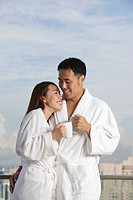 Young couple in robes smiling at each other
