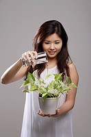 Chinese woman watering a green plant