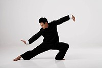 Man doing Tai Chi wearing traditional Chinese clothes