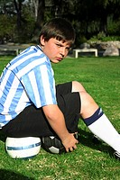 Youthful football player takes a break from practise by sitting on 2 footballs.