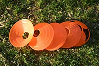 group of orange practise cones on grass field