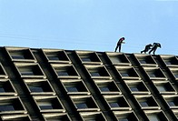 Three men abseiling a building