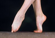 gymnast pointing toes on beam