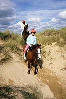 Horse riders on sand dunes