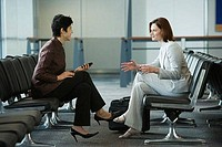 Two businesswomen talking at an airport
