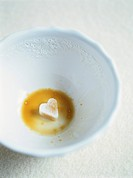 Dregs of café au lait with heart_shaped sugar lump