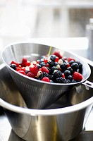 Wild strawberries in a conical strainer