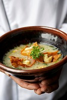 Chef holding a bowl of shrimp congee with wontons