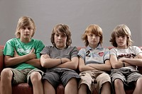 Four boys with arms folded sitting on a sofa