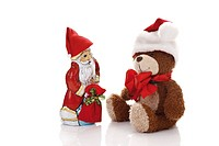 Teddy bear wearing a Christmas cap and a chocolate Santa Claus