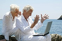 senior citizen couple with notebook at sea side
