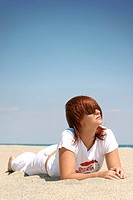young redhaired woman with sunglasses lying on the beach