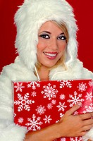 Sexy blond snow bunny in a white furry coat and fur cap holding a Christmas present