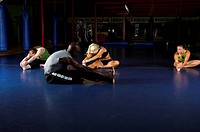 women MMA team and trainer stretching out during a warm up in a boxing gym