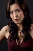 A serious_looking pretty asian woman on black background