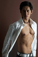 A muscular Asian model in a white open shirt and jeans