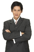 A smart asian businessman with folded arms give a slight smile