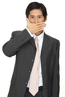 A smart asian businessman, holding his hand in front of his mouth