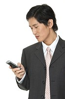 A smart asian businessman writing an SMS