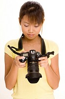 A female photographer checks her last shot on the LCD preview screen of a digital SLR