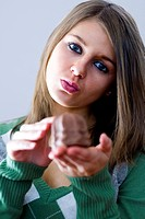 young woman pursing her lips towards a chocolate marsmallow in her hand