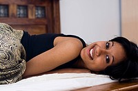 dark_skinned woman lying in bed is posing for the camera