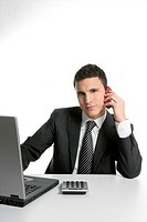 Businessman with headphones and laptop hearing mp3 music