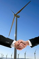 Businessmen handshake environmental agreement over wind mills