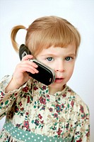 Funny toddler blond girl talking with mobile cell phone