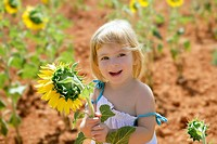 Beautiful little girl in a summer sunflower colorful field