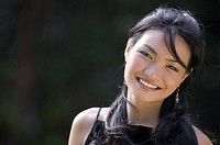A pretty young asian model with a great smile poses outside