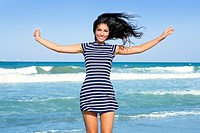 Beautiful summer indian brunette girl jumping on the blue beach