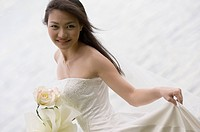 A beautiful young asian woman in a wedding dress. Shot with a lake in the background