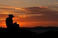 Young woman reading at sunset at the westcoast of Vancouver Island, Canada, Vancouver Island
