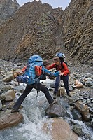 Two hikers, backpackers, women, crossing creek, helping, Donjek Route, St. Elias Mountains, Kluane National Park, Yukon Territory, Canada, North Ameri...
