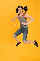 Young woman jumping with Nintendo wii, portrait