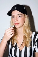 Female sports official preparing to blow whistle