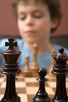 Chess pieces on chess board with boy in background