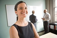 Young businesswoman smiling while businessmen discussing in background
